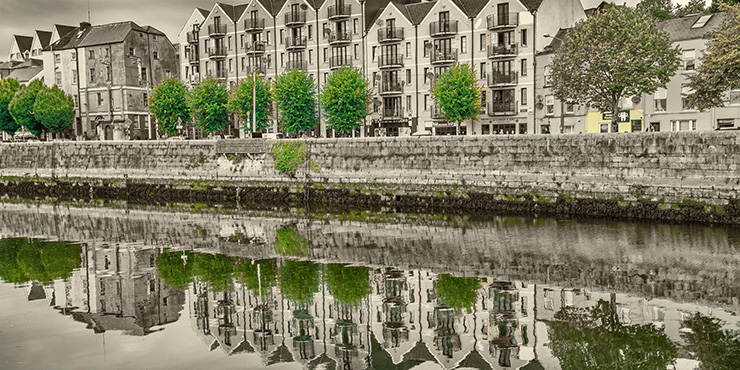 coloured houses in cork with reflection in river lee